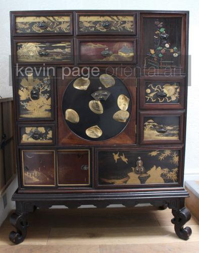 A fine japanese wood cabinet decorated with intricate lacquer panels
