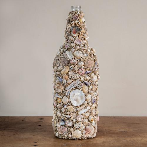 A bottle covered with shells