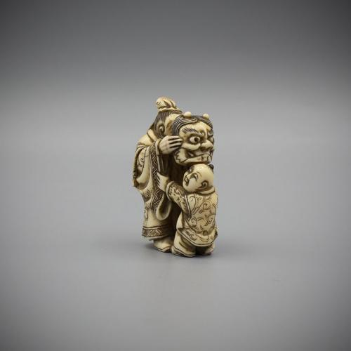 Ivory Netsuke of a Man Teasing a Karako with an Oni Mask by Hidemasa