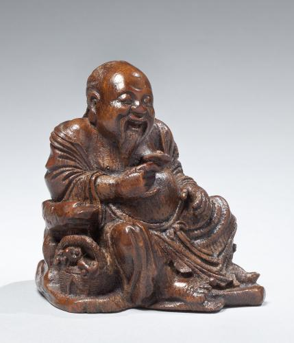 A bamboo figure of a seated gentleman holding a sprig of lingzhi fungus